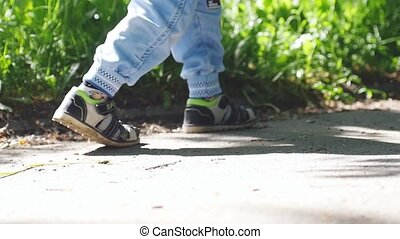 Toddler runs in the park enjoying sunny day in slow motion....