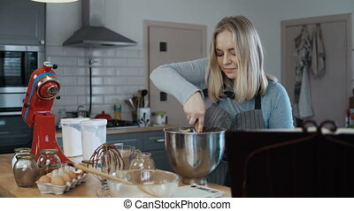 Young beautiful woman mixing the ingredients in a bowl,...