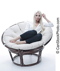 beautiful young woman sitting on the couch in a large...