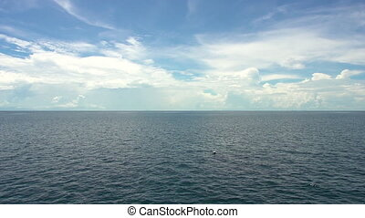 Ocean sky and divers - A wide shot of the ocean's horizon...