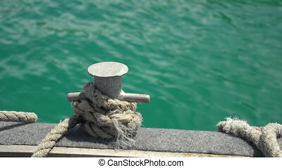 Rope tied up on boat - A medium shot of a rope on a metal on...
