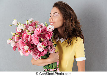 Pretty young girl smelling flower bouquet while standing...
