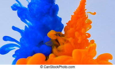 Macro concept of multicolored inks falling and mixing in water abstract background