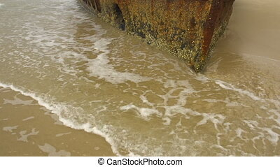 Rusted boat on beach - A full shot of a rusted boat on...