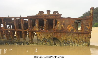 Beach with rusted boat - A medium shot of a rusted boat on...