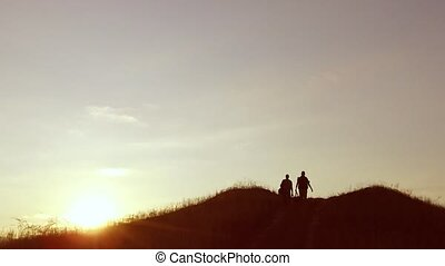 people group of tourists walking on top of a travel sunset silhouette mountain. slow video tourists people group go nature