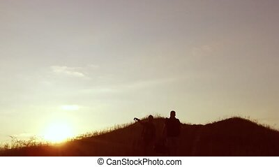 people group of tourists walking on top of a sunset silhouette travel mountain. slow video tourists people group go nature