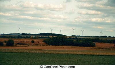 Distant spinning wind generators and field in Austria as...