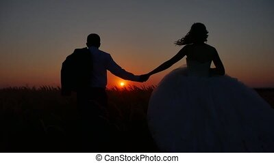 loving couple is running across the field silhouette. loving...