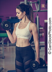 Active young woman work out her arms in fitness club gym