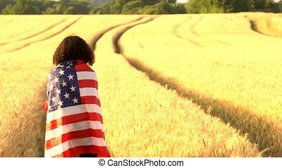 female young woman holding an American USA Stars and Stripes flag in a wheat field