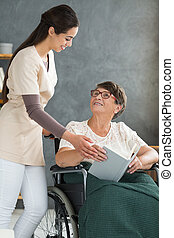 Disabled woman discussing book - Senior, disabled woman...
