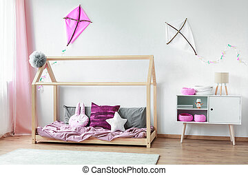 Bed against wall with kites - Shaped pillows on bed and...