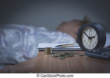 woman sleeping in her bed at night, she is resting with alarm clock.