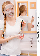 Happy young woman having mud mask on face - Facial dry skin...