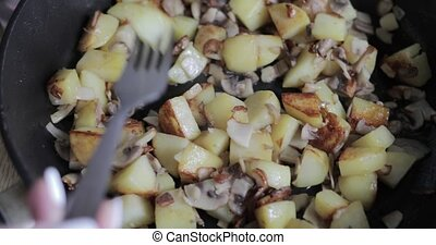 Potatoes with mushrooms in a frying pan