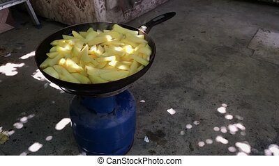 Fried potatoes in a frying pan on a gas burner in the yard