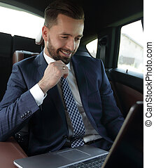 businessman reads information on laptop while sitting in car...