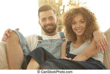 Young couple in work clothes sitting on couch in new house