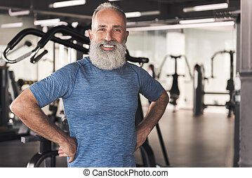 Positive old male with beard is relaxing in sport club -...