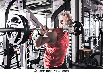 Serious mature male is having intense workout in gym - Heavy...