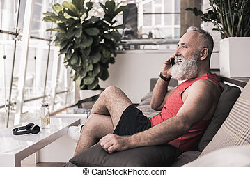 Cheerful old male is having pleasant conversation on...