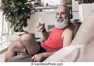 Cheerful old male is sitting on couch in sport center -...
