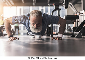Bearded old pensioner male is having workout in gym -...