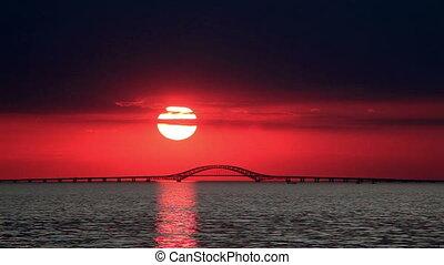 Big Red Sun Setting Over Bridge - Time Lapse