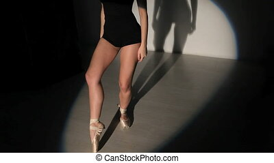 Closeup legs of dancing ballerina in spotlight