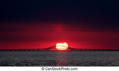 Big Red Sun Setting Over Bridge - Time Lapse