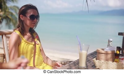 Young woman wearing sunglasses drinking cocktail in summer...