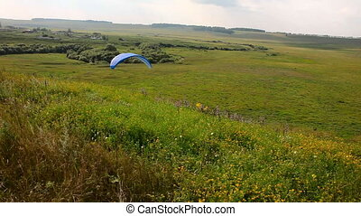 Paraplane - Paraglider lands on the lawn near the village