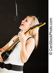 Woman playing on electric guitar and singing - Music,...