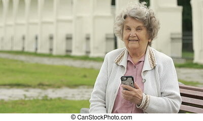 Elderly woman holds silver smart phone outdoors