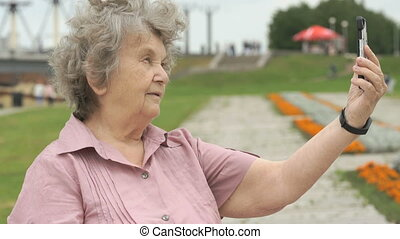 Elderly woman takes photos using a mobile phone - Elderly...