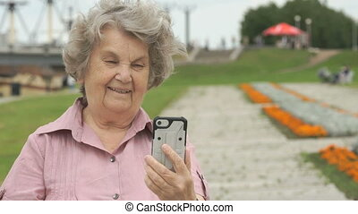 Elderly woman takes photos using a mobile phone
