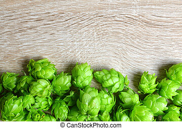 Hop cones (Humulus Lupulus)  on wooden background.