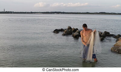 Man Casting Net - Young adult man uses a cast net to catch...