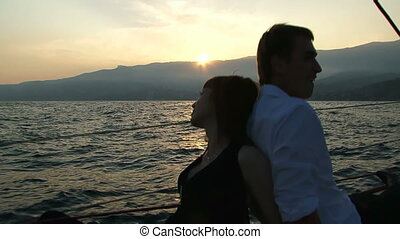 Romantic getaway - Young couple sitting on a yacht on the...