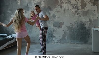 Carefree family with daughter dancing in the room -...