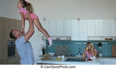 Affectionate dad raising daughter up in the kitchen -...