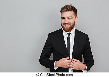 Smiling handsome businessman in suit standing and laughing...