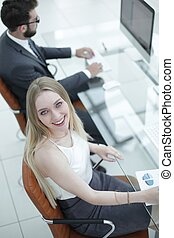 young business woman sitting at a desk in the office . -...