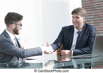 Two business colleagues shaking hands during meeting -...