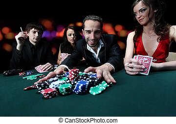 Poker players sitting around a table at a casino - Group of...