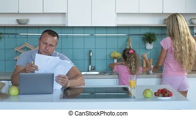 Stressed man browsing bills and documents at home - Family...