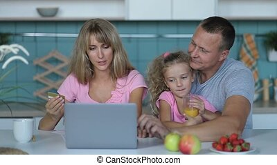 Joyful family shopping online with laptop at home