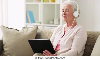 senior woman with tablet pc and headphones at home -...