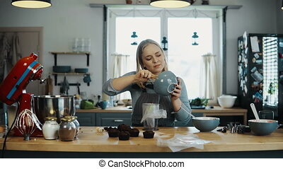 Young blonde woman cooking in the kitchen. Beautiful female preparing cream for decorating cupcakes, doing her hobby.